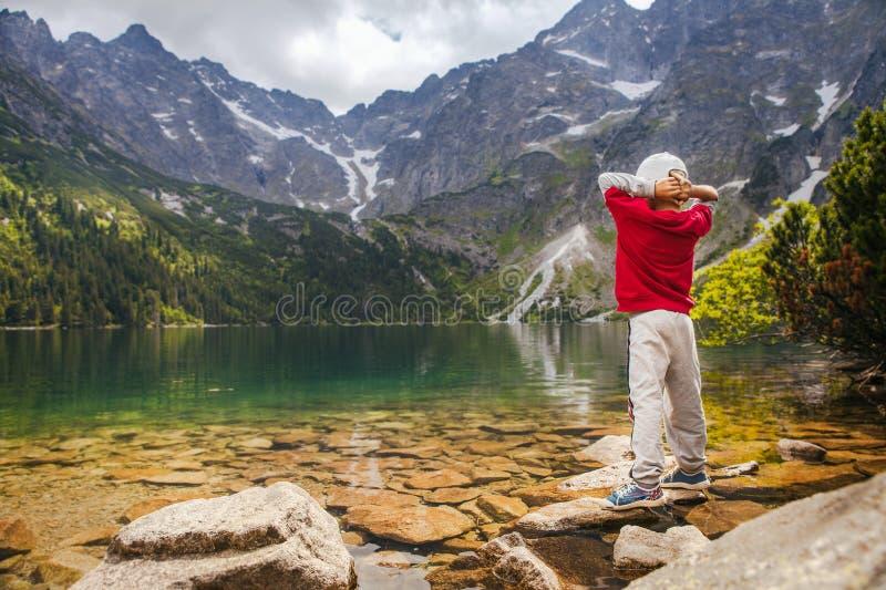 El niño pequeño se relaja en costa del lago de la montaña foto de archivo