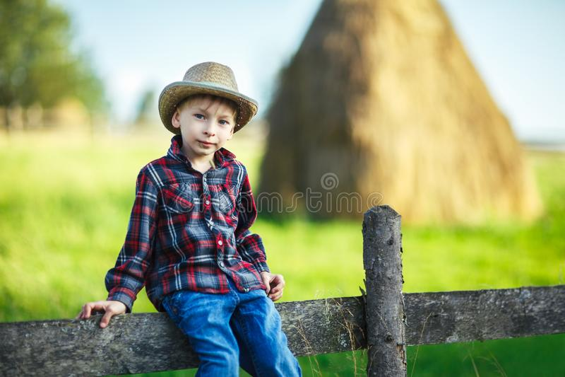 El niño pequeño se sienta en la cerca de madera contra pajar pintoresco fotografía de archivo