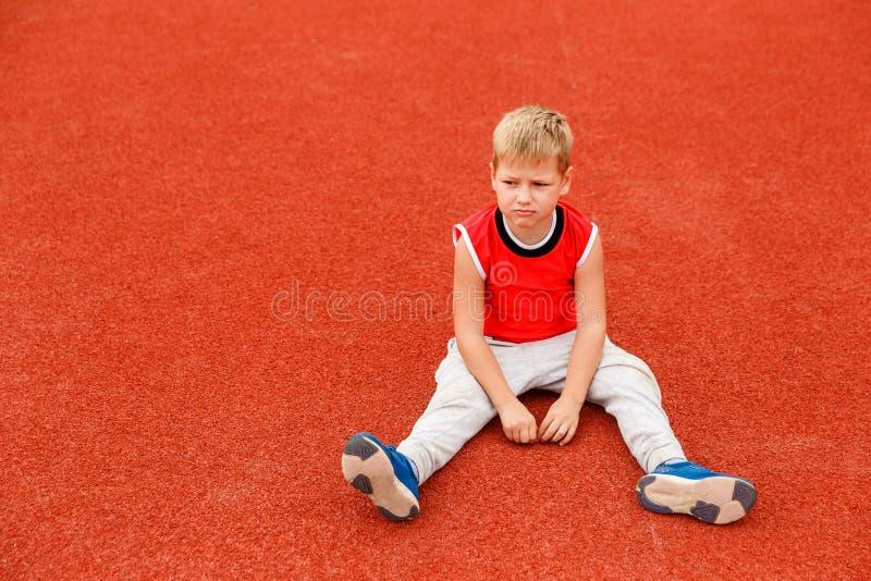 El niño pequeño se sienta en la cubierta roja al aire libre imagen de archivo libre de regalías