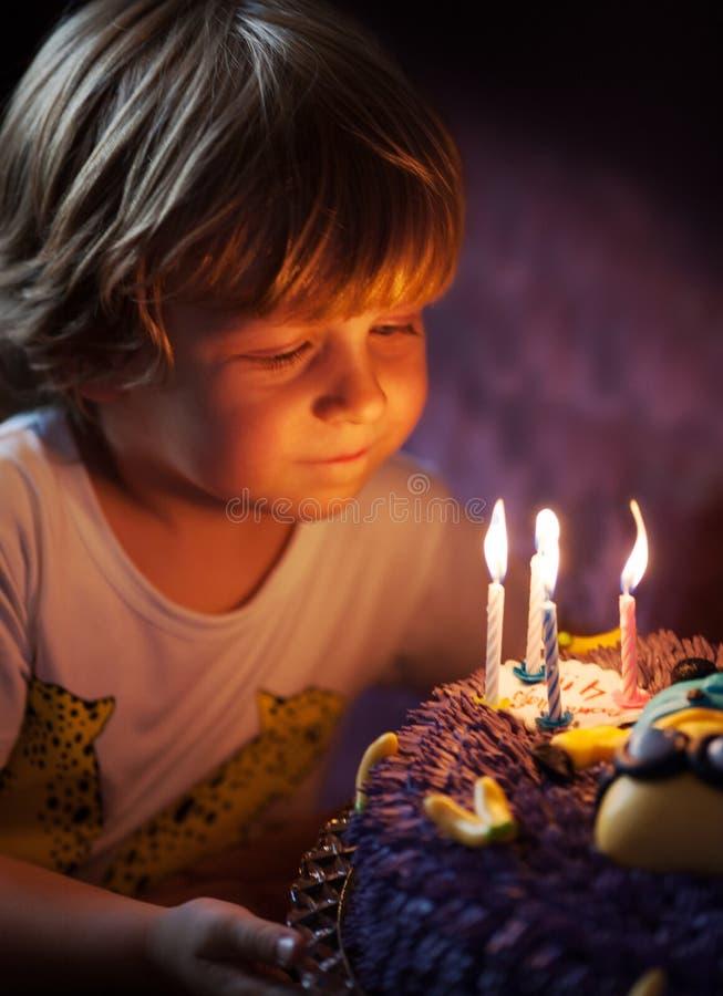 El niño pequeño sopla hacia fuera velas en su cumpleaños imagen de archivo