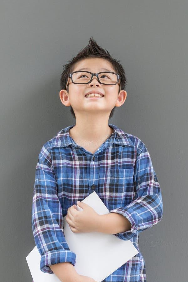 El niño pequeño sostiene el libro con las manos que tienen felicidad contra la pared gris imágenes de archivo libres de regalías