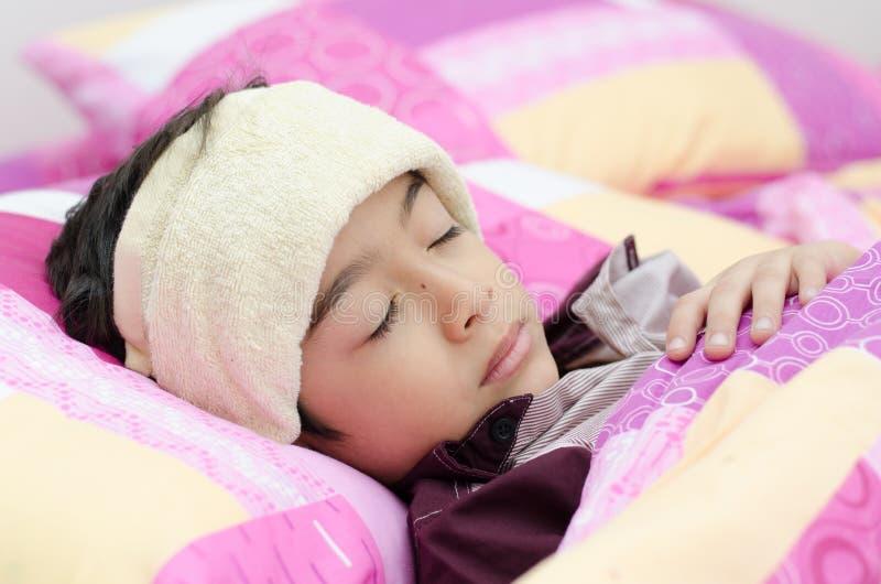 El niño pequeño tiene fiebre con la toalla en la cabeza imagenes de archivo