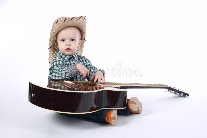 El niño pequeño toca la guitarra en blanco fotografía de archivo libre de regalías