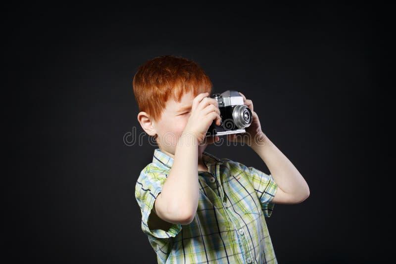 El niño pequeño toma la foto con la cámara del vintage en el fondo negro imagenes de archivo