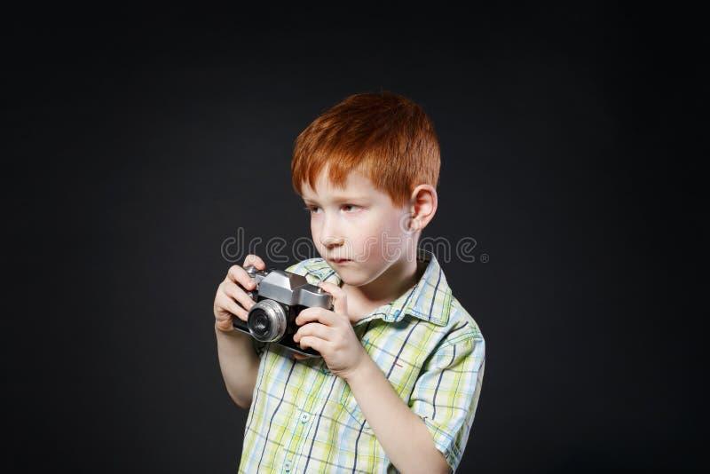 El niño pequeño toma la foto con la cámara del vintage en el fondo negro imagen de archivo libre de regalías