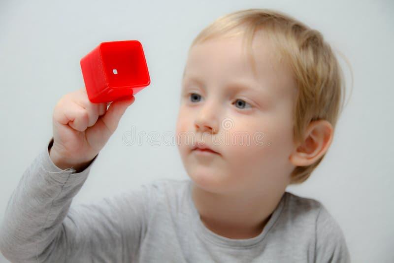 El niño pequeño tres años se sienta en la tabla y los juegos con los plas imágenes de archivo libres de regalías
