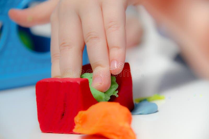 El niño pequeño tres años se sienta en la tabla y los juegos con plasticine y los juguetes, los cubos y los dados de madera y plá foto de archivo