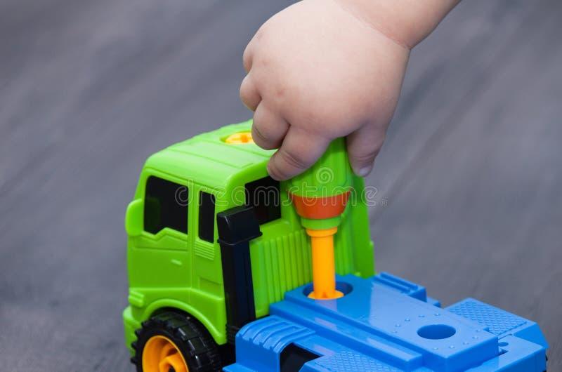 El niño pequeño tuerce el perno con un destornillador Juegos del niño con el coche del juguete del plastick fotografía de archivo