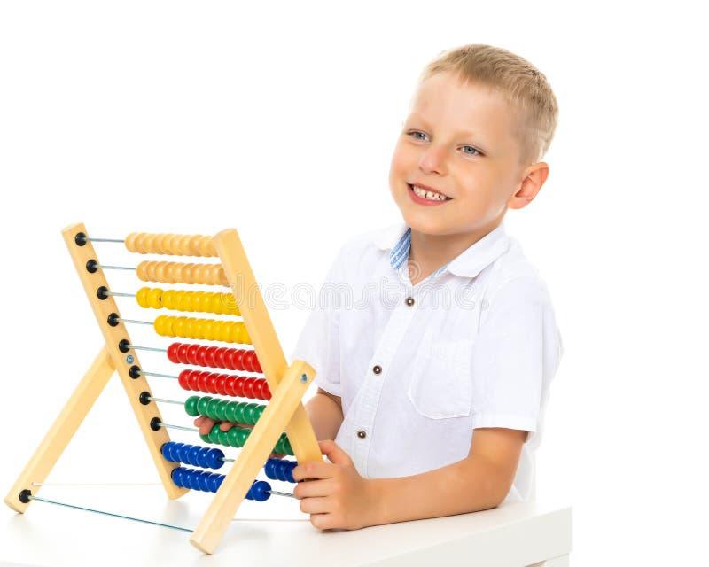 El niño pequeño utiliza el ábaco para solucionar problemas matemáticos imágenes de archivo libres de regalías