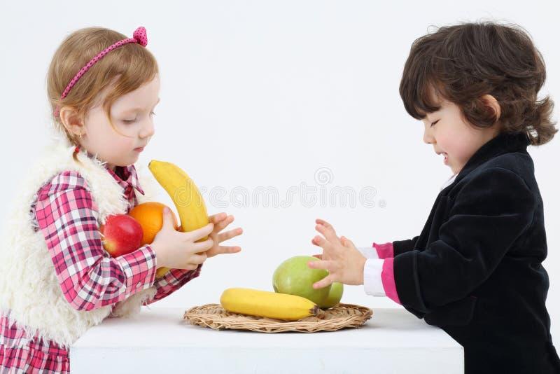 El niño pequeño y la muchacha colocan y toman las frutas de la tabla blanca imagenes de archivo