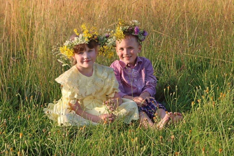 El niño pequeño y la muchacha felices en guirnaldas se sientan en la hierba seca a foto de archivo