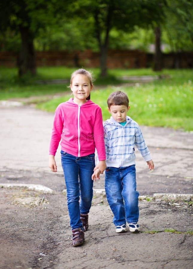 El niño pequeño y la muchacha van para un paseo foto de archivo libre de regalías