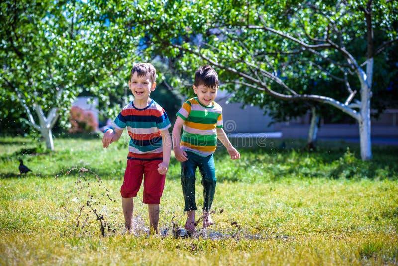 El niño pequeño y su hermano juegan en parque del verano Niños con el co fotos de archivo