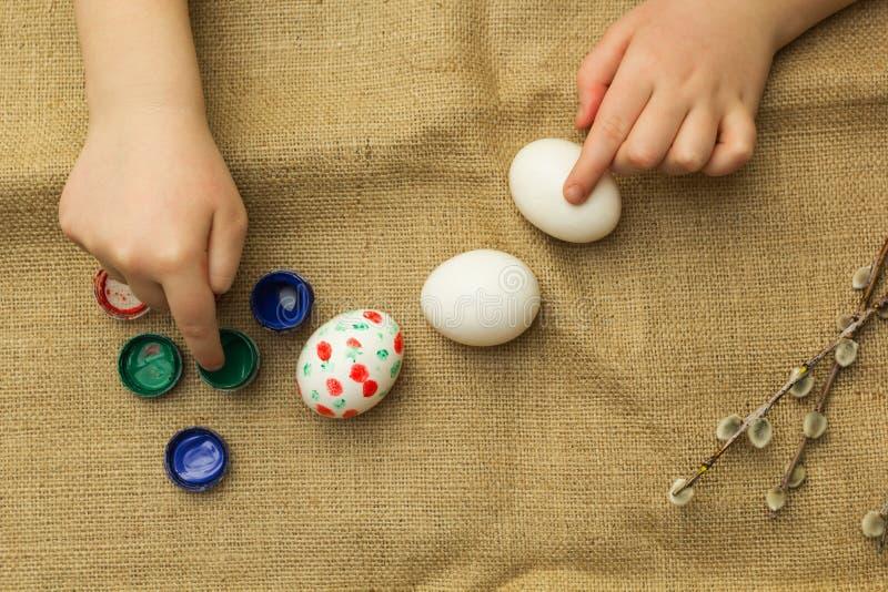 El niño pinta los huevos para Pascua libre illustration