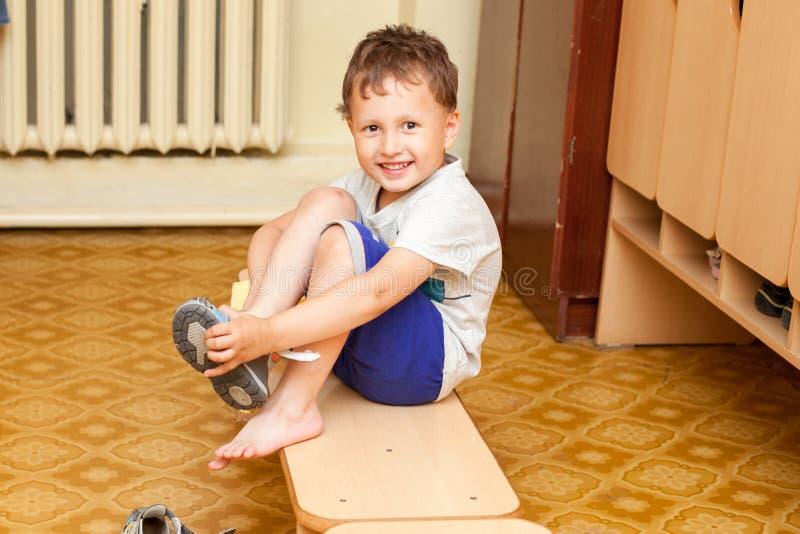 El niño pone los zapatos en guardería imagenes de archivo
