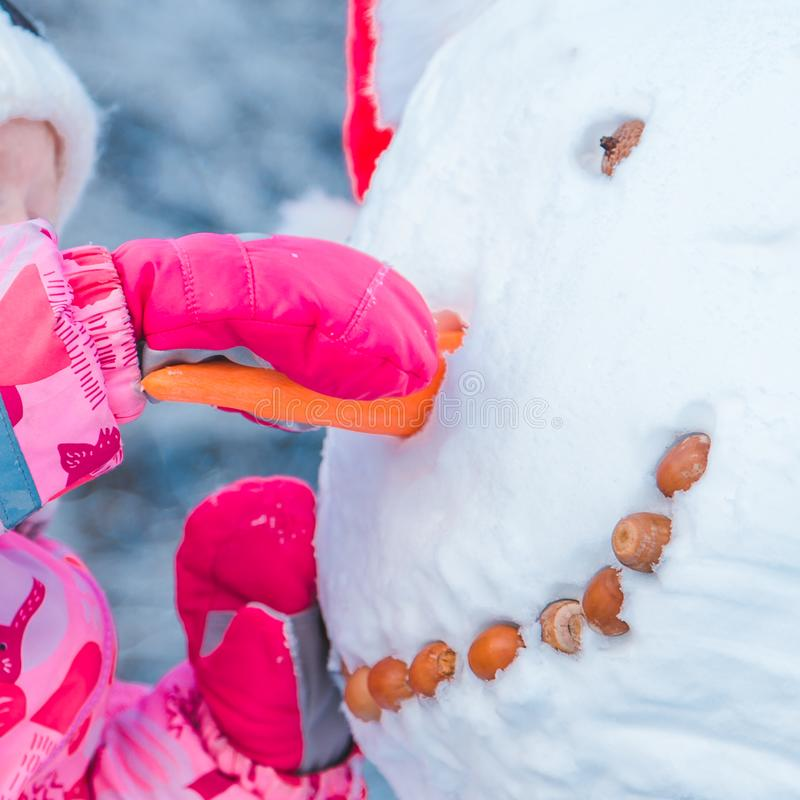 El niño puso la nariz de la zanahoria para el muñeco de nieve fotos de archivo libres de regalías