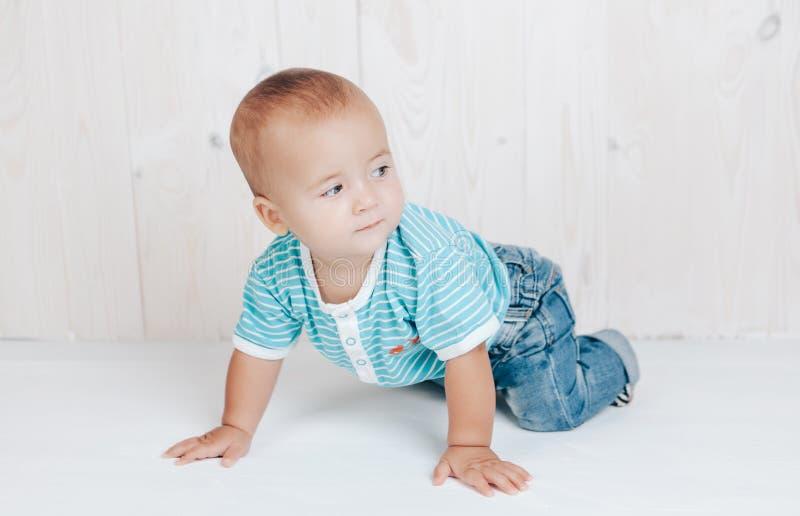 El niño que descansa sobre sus manos mira misterioso al lado en un fondo ligero fotografía de archivo