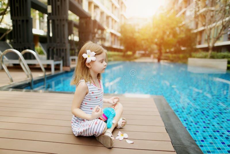 El niño que hace yoga ejercita sentarse cerca de la flor que lleva de la piscina el día soleado fotos de archivo libres de regalías