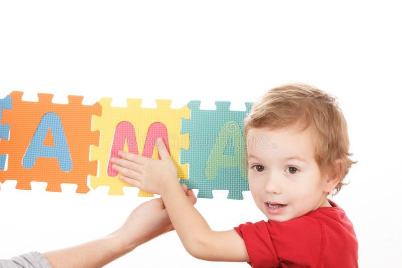 El niño que juega con alfabeto del ABC de los bloques del rompecabezas, monta foto de archivo libre de regalías