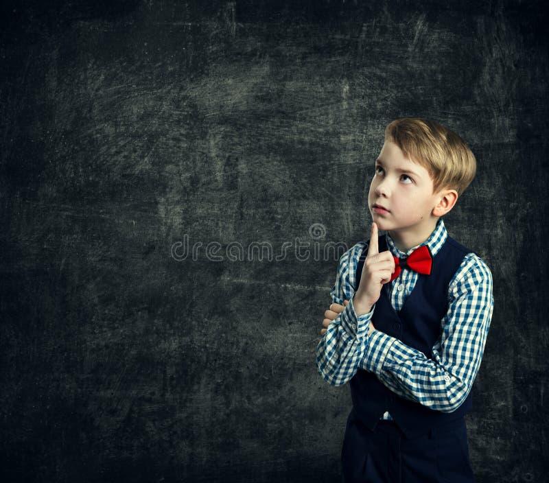 El niño que piensa sobre la pizarra de la escuela, muchacho del niño piensa la educación fotos de archivo