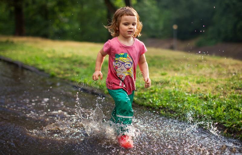 El niño que salta en charco del agua foto de archivo