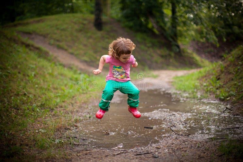 El niño que salta en charco del agua foto de archivo libre de regalías