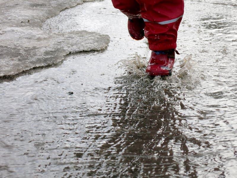 El niño que salta para los charcos en los caminos deshiela en finales del invierno foto de archivo