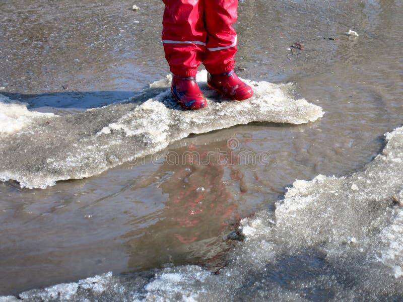 El niño que salta para los charcos en los caminos deshiela en finales del invierno fotos de archivo libres de regalías