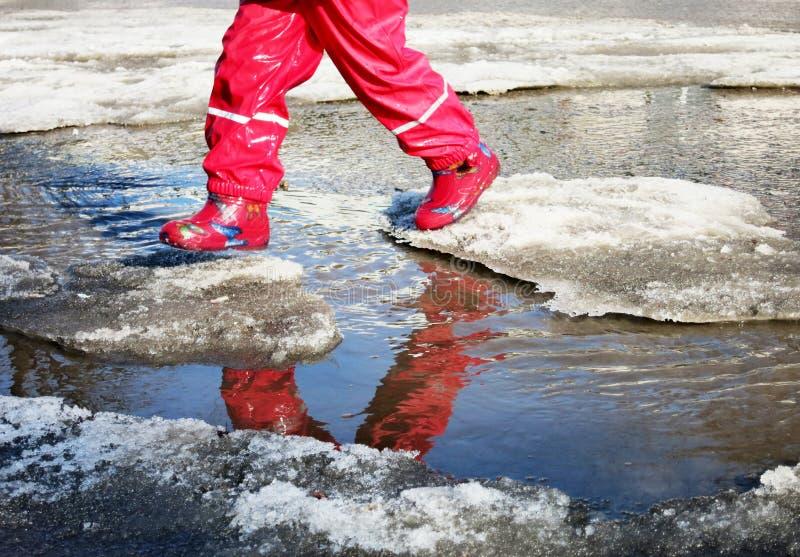 El niño que salta para los charcos en los caminos deshiela en finales del invierno imágenes de archivo libres de regalías