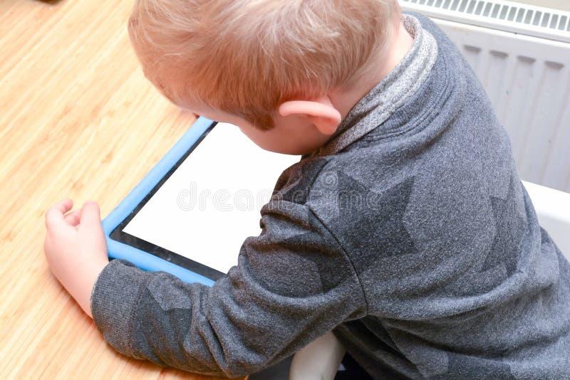 El niño que usa una tableta para aprender y para jugar a los juegos, modelo es muchacho joven imagen de archivo
