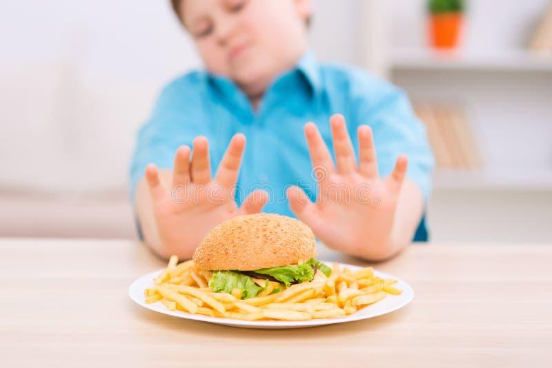 El niño rechoncho rechaza comer la comida malsana imagen de archivo libre de regalías