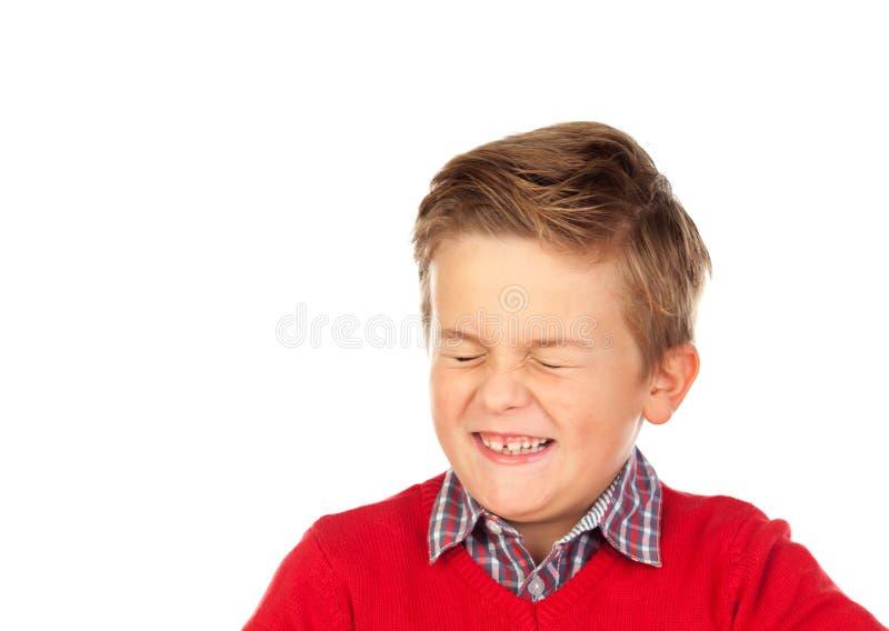 El niño rubio con una expresión divertida que cierra el suyo observa fotografía de archivo
