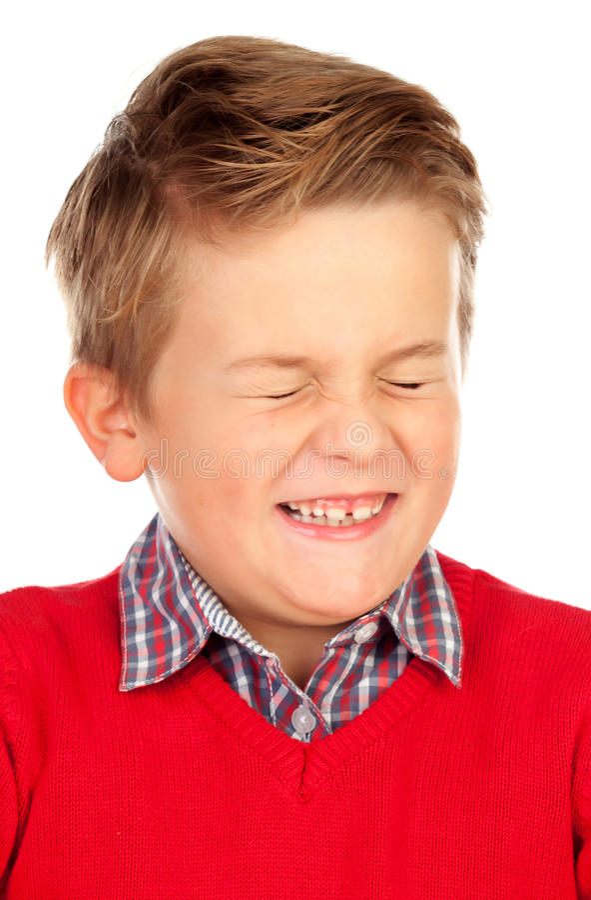 El niño rubio con una expresión divertida que cierra el suyo observa foto de archivo