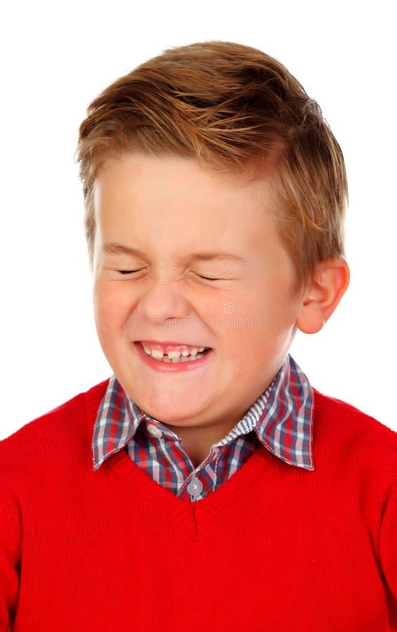 El niño rubio con una expresión divertida que cierra el suyo observa fotografía de archivo libre de regalías