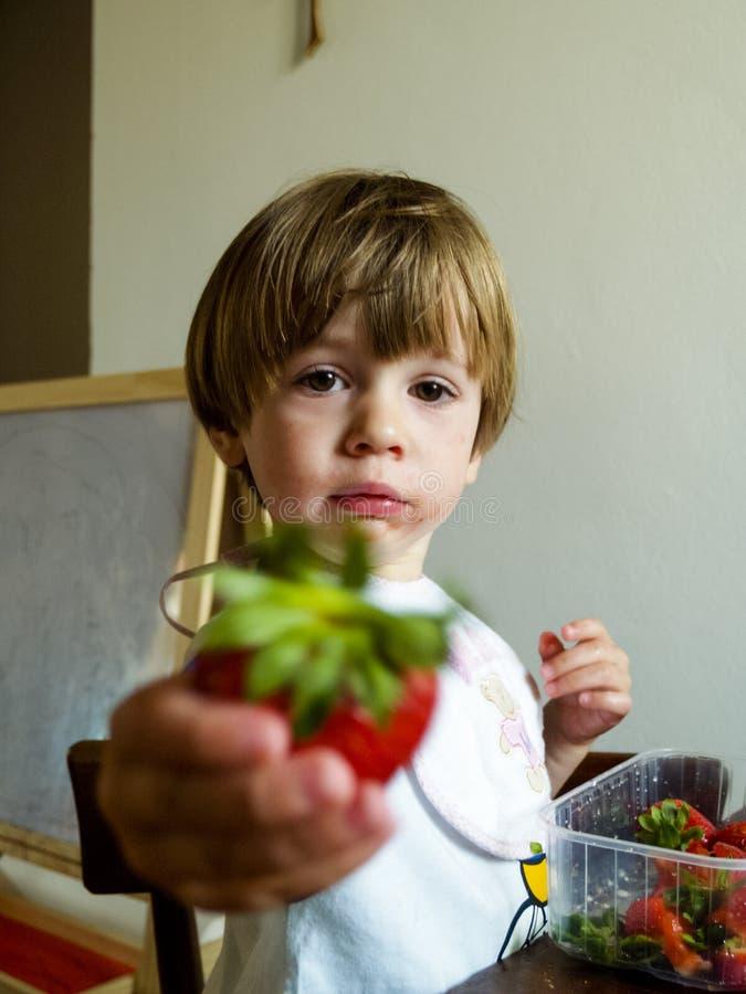 El niño rubio de 3 años come una fresa grande imagenes de archivo