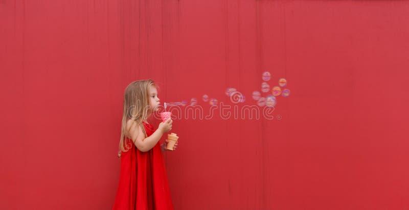 El niño rubio de la muchacha en vestido rojo en un fondo de la pared sopla burbujas fotos de archivo libres de regalías
