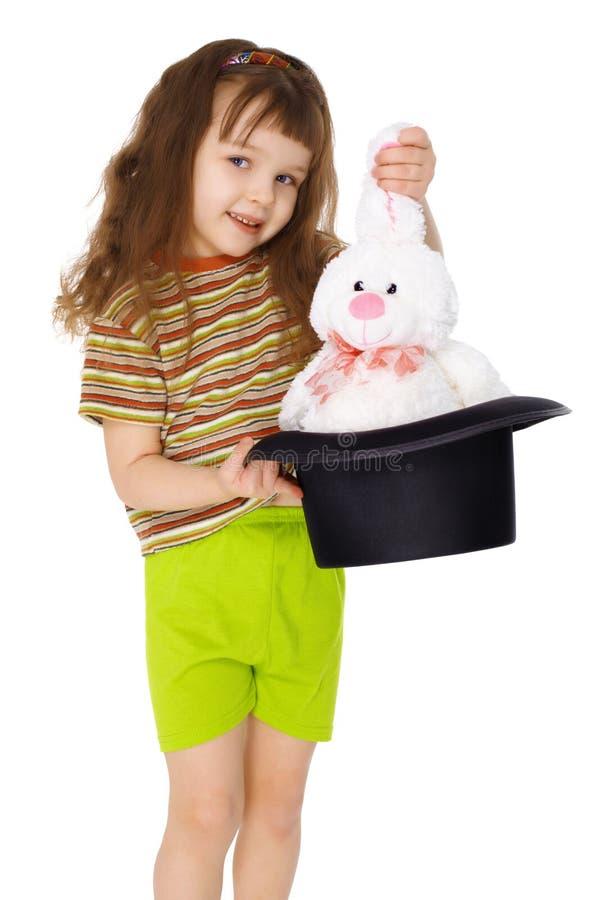 El niño sale el conejo del sombrero como mago foto de archivo