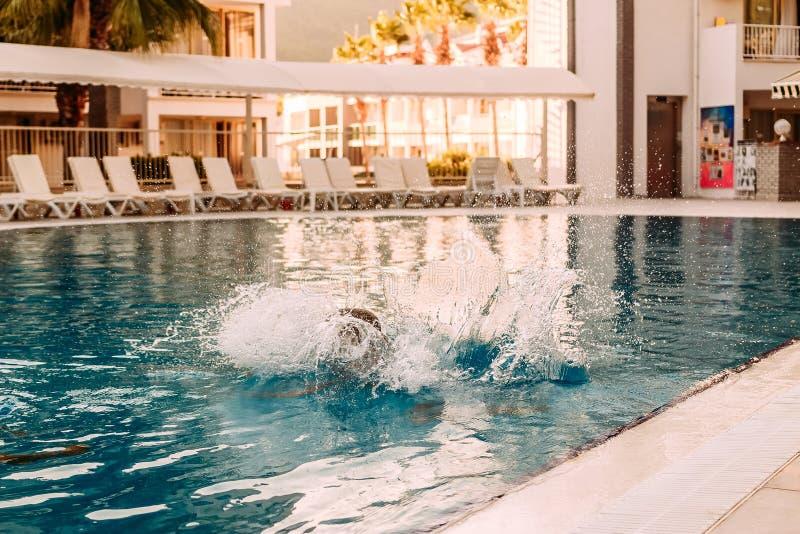 El niño saltó en la piscina al aire libre y sumergido debajo del agua, grande salpica imagen de archivo