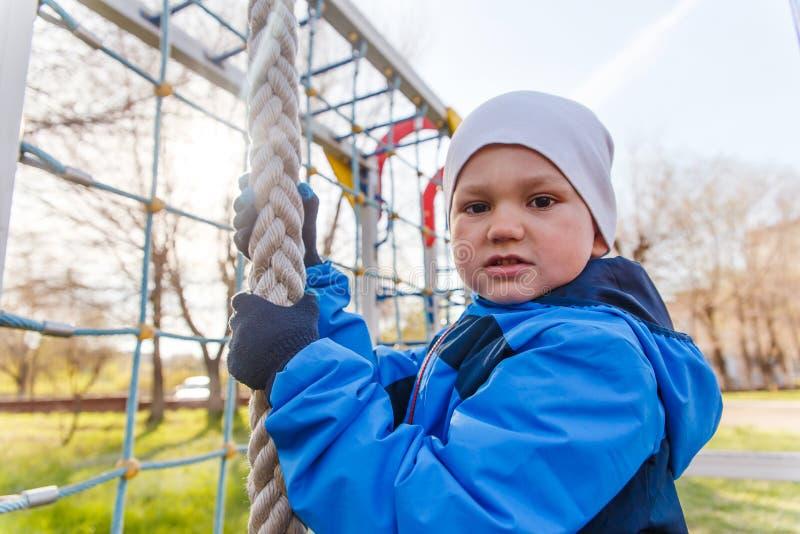 El niño se aferra en la cuerda en el patio del ` s de los niños foto de archivo libre de regalías