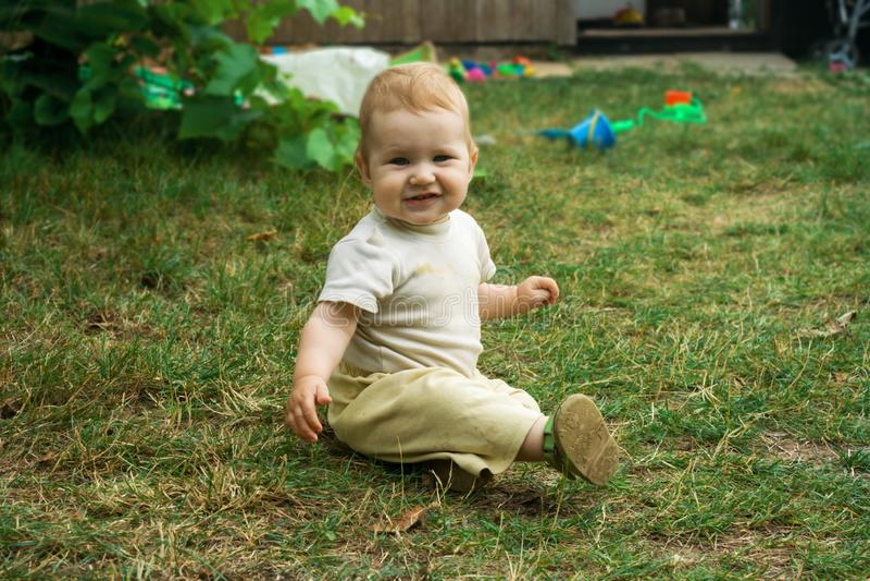El niño se arrastra y se sienta feliz en la hierba verde Sonrisas y movimientos del niño en todos los fours alrededor de la yarda imagenes de archivo
