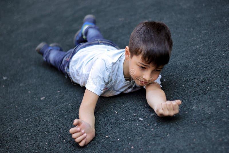 El ni?o se cay? y golpe? su mano, el muchacho tropez? y se cay? en la acera imagen de archivo