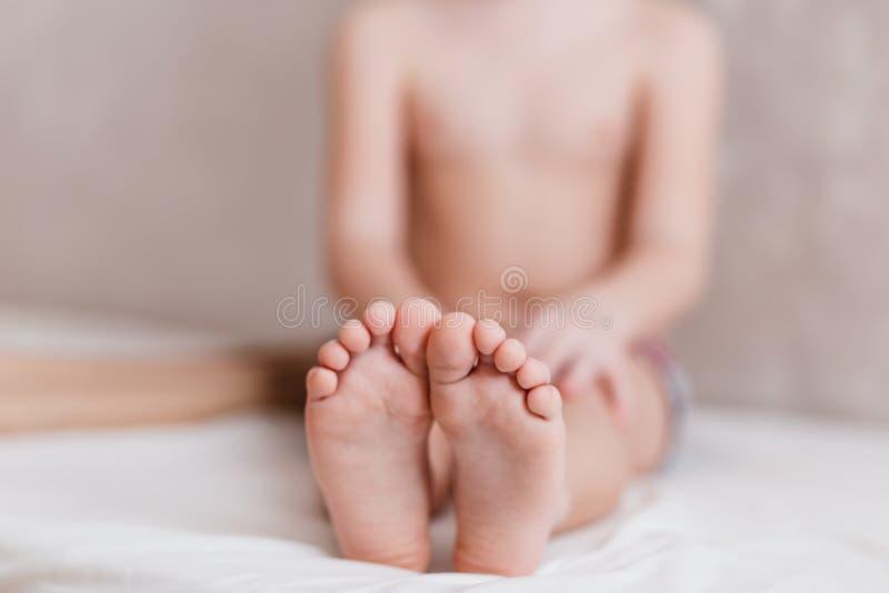 El niño se está sentando descalzo en la cama, niños descubre pequeños pies foto de archivo libre de regalías
