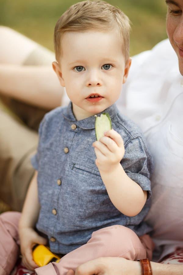 El niño se sienta al lado de su padre en el parque en la manta ?l est? comiendo fotos de archivo libres de regalías