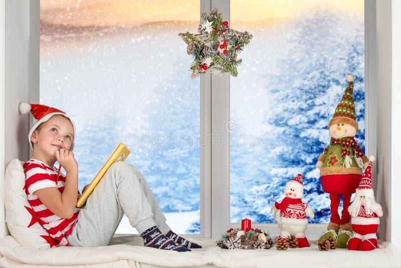 El niño se sienta en la ventana y escribe una letra a Santa Claus ¡Feliz Navidad y buenas fiestas! imagen de archivo libre de regalías