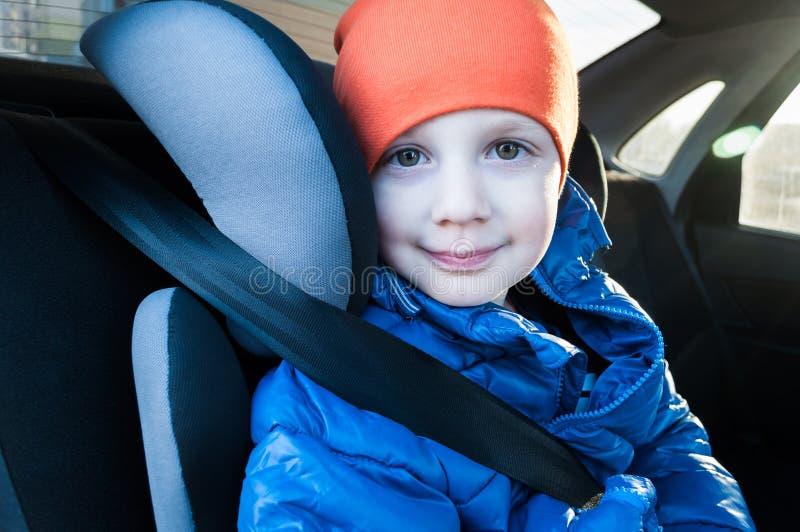 El niño se sienta en un asiento de auto, sujeto con un cinturón de seguridad Transporte seguro de un niño o niños en un automóvil imagen de archivo