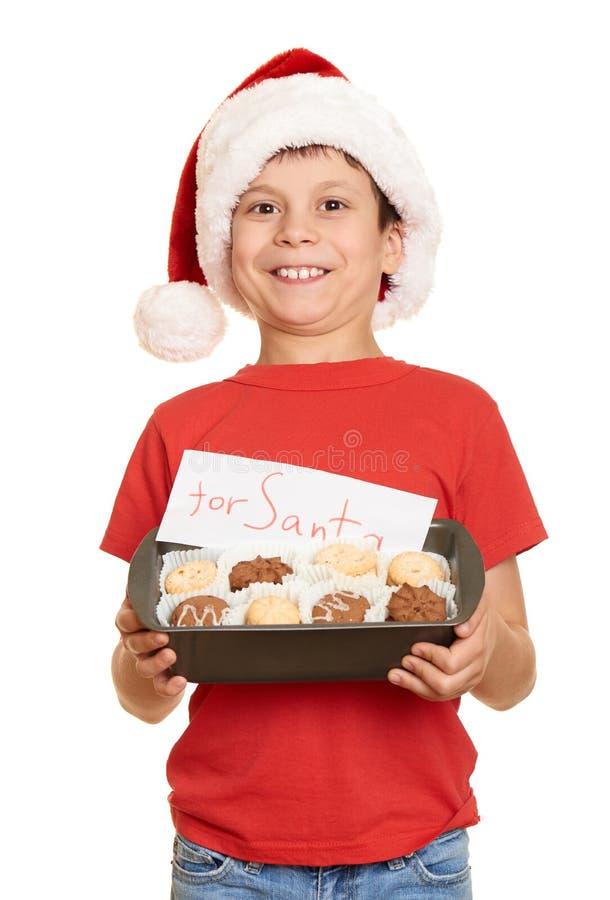 El niño se vistió en el sombrero de santa aislado en el fondo blanco Noche Vieja y concepto de las vacaciones de invierno fotos de archivo