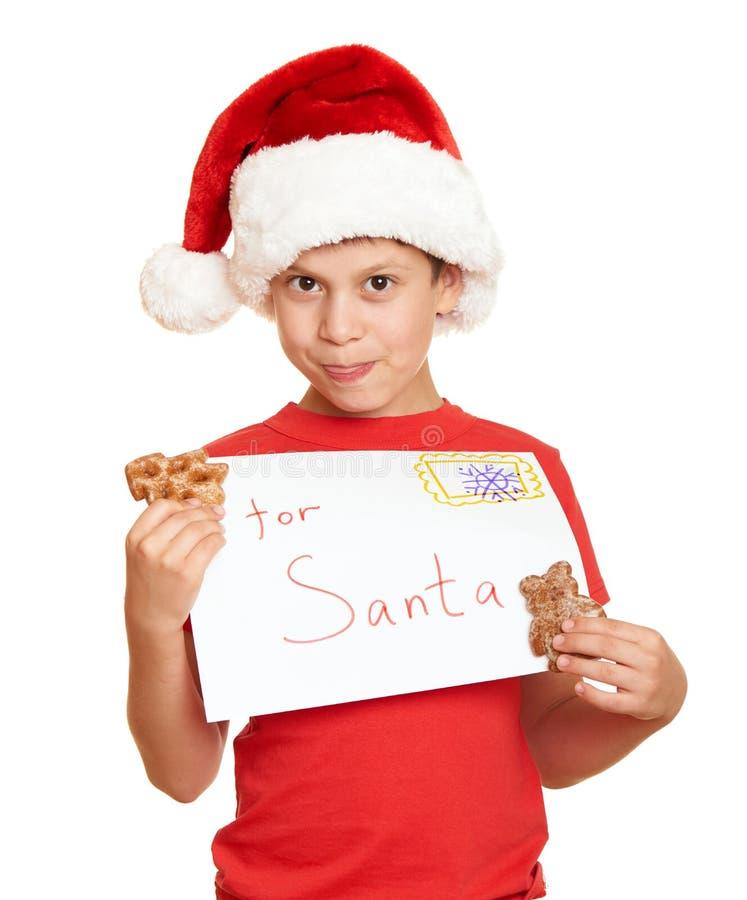 El niño se vistió en el sombrero de santa aislado en el fondo blanco Noche Vieja y concepto de las vacaciones de invierno fotografía de archivo libre de regalías