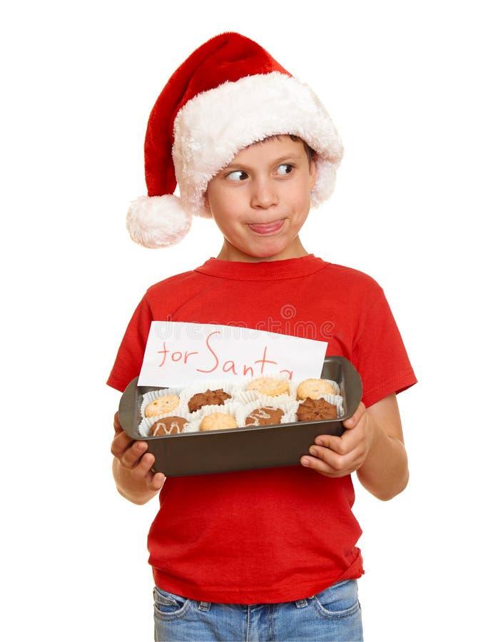 El niño se vistió en el sombrero de santa con las galletas aisladas en el fondo blanco Noche Vieja y concepto de las vacaciones d foto de archivo