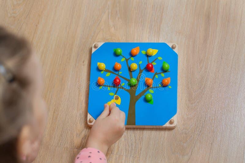 El niño separa el color de las bolas de madera Juego para los niños imagenes de archivo