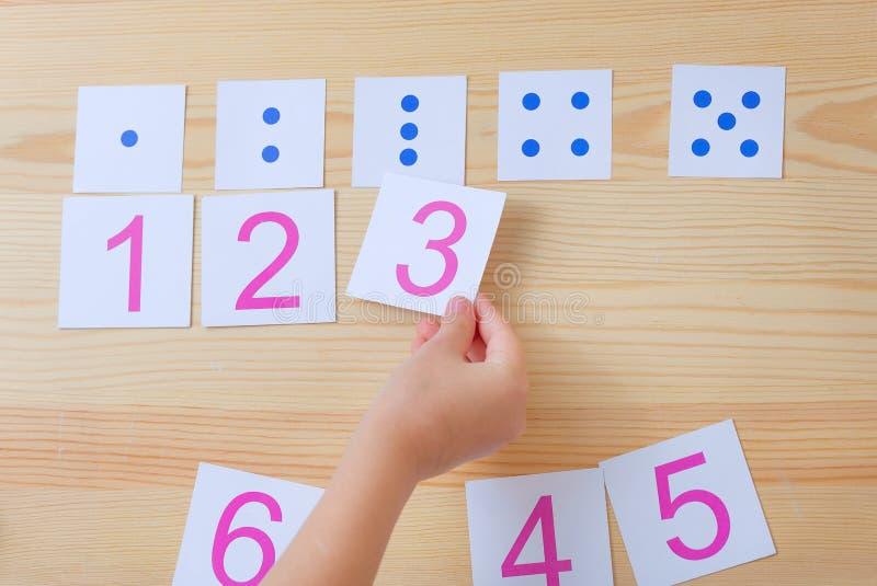 El niño separa tarjetas con números a las tarjetas con los puntos El estudio de números y de matemáticas foto de archivo